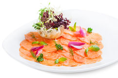 Salmon carpaccio with salad on plate.  royalty free stock photos
