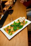 Salmon carpaccio on a white plate with a glass of red wine royalty free stock photography