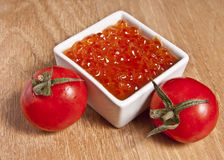 Salmon caviar. And two cherry tomatoes on wooden board Royalty Free Stock Image