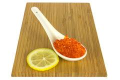 Salmon caviar. Asian spoon with salmon caviar and lemon slice on wooden plate Royalty Free Stock Photo