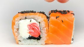 Chef luxury sushi rolls japan cuisine restaurant presentation slowmotion on white black sesame seeds falling. Salmon cheese ginger black sesame seeds chef luxury stock footage