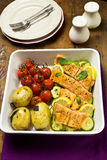 Salmon with cherry tomatoes, courgettes and baby potatoes Royalty Free Stock Images