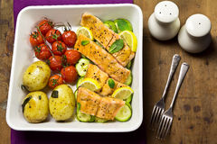 Salmon with cherry tomatoes, courgettes and baby potatoes Stock Photo