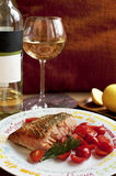 Salmon with cherry tomatoes and glass of white wine. Salmon/trout with cherry tomatoes and glass of white wine Stock Images
