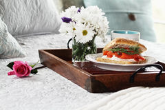 Salmon on Ciabatta Breakfast in Bed. Salmon on Ciabatta Breakfast in and flowers served in bed for Mother's Day royalty free stock image
