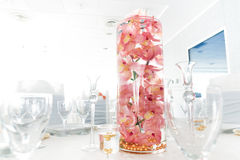 Salmon colored (light pink) orchids in a water glass decorate on Royalty Free Stock Photography