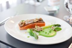 Salmon cooked with crispy skin. Served with gree peas and asparagus spears Stock Photos