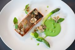 Salmon cooked with crispy skin. Served with gree peas and asparagus spears Stock Photo