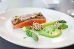 Salmon cooked with crispy skin. Served with gree peas and asparagus spears Royalty Free Stock Photography