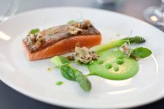 Salmon cooked with crispy skin. Served with gree peas and asparagus spears Royalty Free Stock Photos