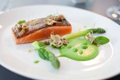 Salmon cooked with crispy skin. Served with gree peas and asparagus spears Royalty Free Stock Photo