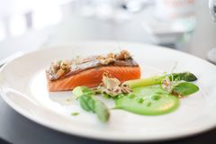 Salmon cooked with crispy skin. Served with gree peas and asparagus spears Stock Photography