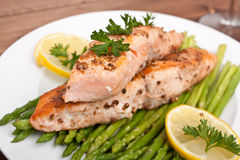 Salmon with coriander seeds and asparagus. Healthy Salmon with Coriander Seeds Garnished with Asparagus and Lemon Wedges Stock Image