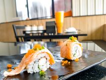 Salmon Cream Sheese Roll with Sasabi Souce on a black plate in Japanese restaurant.  stock photos
