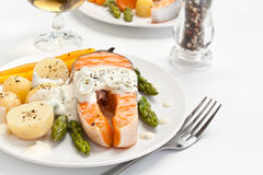 Salmon with creamy asparagus sauce. Potatoes and carrots with fork Royalty Free Stock Image