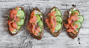 Salmon, cucumber and cream cheese rye sandwich on the wooden background Stock Image
