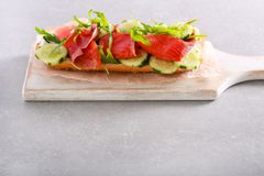 Salmon, cucumber, rocket and creamcheese sandwich. On board stock photography