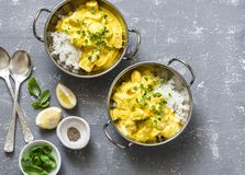 Salmon curry and rice in curry dishes on grey background, top view. Indian cusine style. Stock Photos