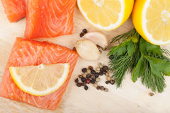 Salmon on cutting board with lemons and herbs Stock Photography