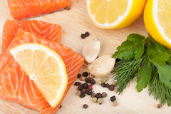 Salmon on cutting board with lemons and herbs Royalty Free Stock Images
