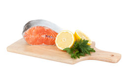Salmon on cutting board with lemons and herbs Stock Image