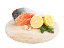 Salmon on cutting board with lemons and herbs Stock Images