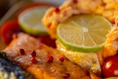 A salmon decorated by spices of pink peppercorn. Macro. stock photo