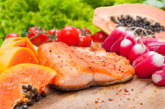 Salmon diet food. Grilled salmon diet fish food closeup with tomato and salad in background Royalty Free Stock Images