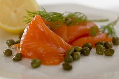 Salmon with dill,capers and lemon. There are some pieces of smoked salmon with dill, capers and lemon on a dish royalty free stock photo