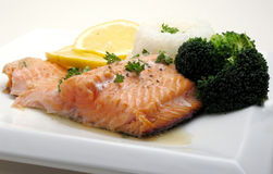 Salmon dinner with broccoli. Salmon trout dinner on white plate with rice, lemon slices and broccoli Stock Photos