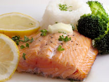 Salmon dinner with butter. Salmon trout dinner with white rice, broccoli, lemon, parsley and butter, on white plate Stock Photos