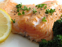 Salmon dinner close-up. Close-up of broiled salmon trout with lemon and broccoli on white plate Royalty Free Stock Photos