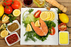 Salmon dish. Raw salmon fish on dish with many other ingredients royalty free stock images