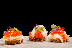 Salmon eggs, fish, and herbs canapes Stock Image