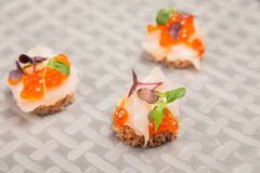 Salmon eggs, fish, and herbs canapes Royalty Free Stock Photo
