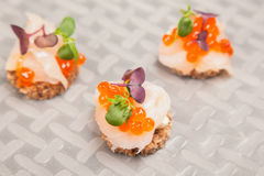 Salmon eggs, fish, and herbs canapes Royalty Free Stock Image