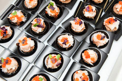 Salmon eggs, fish, and herbs canapes. Appetizer of Salmon eggs, fish, and green herbs canapes Royalty Free Stock Images