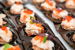 Salmon eggs, fish, and herbs canapes. Appetizer of Salmon eggs, fish, and green herbs canapes Royalty Free Stock Photo