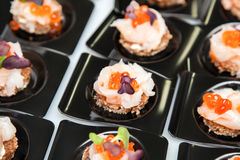 Salmon eggs, fish, and herbs canapes. Appetizer of Salmon eggs, fish, and green herbs canapes Stock Photography