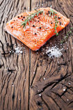 Salmon filet on a wooden carving board. Stock Photos