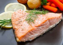 Salmon fillet on asparagus bed on dish Royalty Free Stock Images