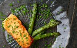 Salmon Fillet With Asparagus en la placa de cristal Fotografía de archivo