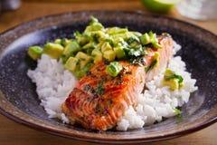 Salmon fillet with avocado lime coriander salsa, rice as a garnish. Horizontal royalty free stock photo