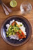 Salmon fillet with avocado lime coriander salsa, rice as a garnish. Overhead, vertical royalty free stock images