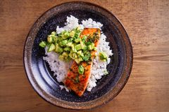 Salmon fillet with avocado lime coriander salsa, rice as a garnish. Overhead, horizontal royalty free stock images