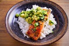 Salmon fillet with avocado lime coriander salsa, rice as a garnish. Horizontal royalty free stock image