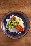 Salmon fillet with avocado lime coriander salsa, rice as a garnish. Overhead, vertical stock photography
