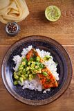 Salmon fillet with avocado lime coriander salsa, rice as a garnish. Overhead, vertical stock images