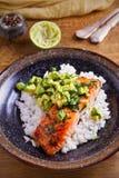 Salmon fillet with avocado lime coriander salsa, rice as a garnish. Vertical stock photo