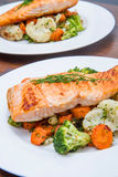 Salmon fillet on a bed of broccoli, cauliflower and carrots Stock Photos